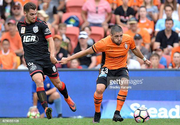 Dimitri Petratos of the Roar is challenged by Benjamin Garuccio of Adelaide during the round 10 ALeague match between the Brisbane Roar and Adelaide...