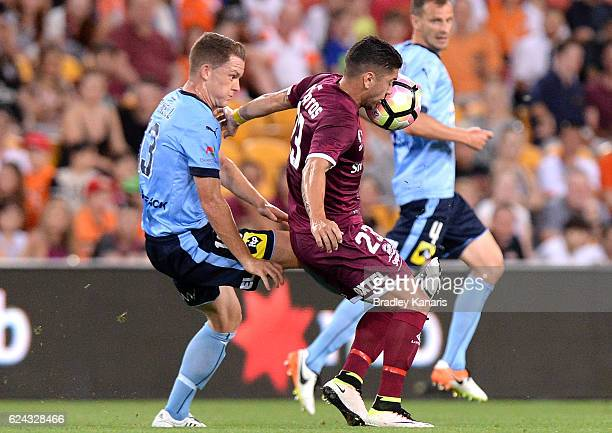 Dimitri Petratos of the Roar is challenged by Brandon O'Neill of Sydney during the round seven ALeague match between the Brisbane Roar and Sydney FC...