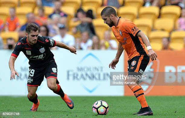 Dimitri Petratos of the Roar takes on the defence of Benjamin Garuccio of Adelaide during the round 10 ALeague match between the Brisbane Roar and...