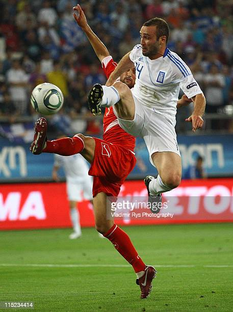 Dimitrio Salpingidis of Greece and Andrew Angus of Malta battle for the ball during the EURO 2012 group F qualifying match between Greece and Malta...