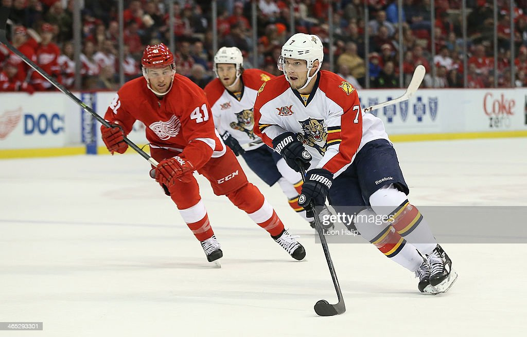 Dimitry Kulikov #7 of the Florida Panthers carries the puck across the blue line as Luke Glendenig #41 of the Detroit Red Wings follows during the second period of the game at the Joe Louis Arena on January 26, 2014 in Detroit, Michigan. The Panthers defeated the Wings 5-4 in a shootout