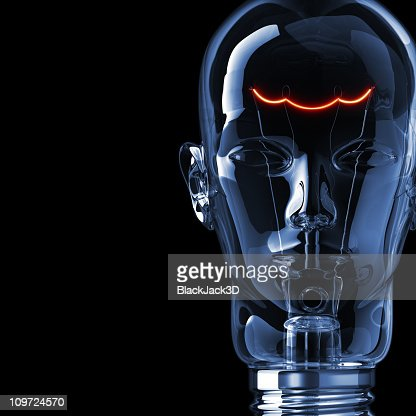 A dimly lit light bulb molded in the shape of a human face : Bildbanksbilder
