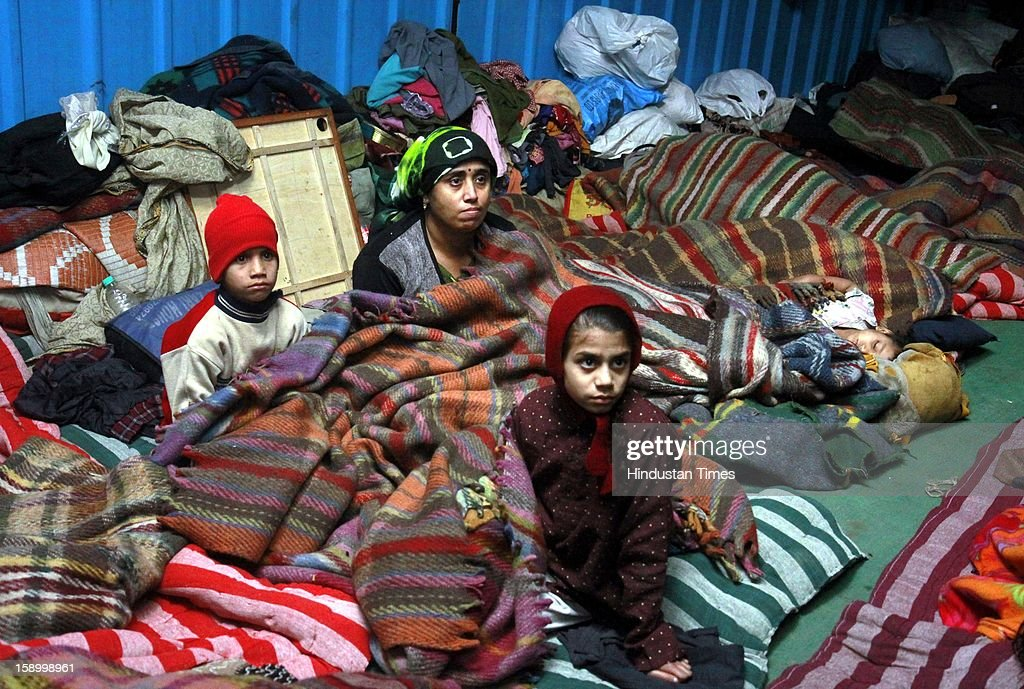 Dimple with her childerns wrapped in a quilt, sits in cold winter night at Baba Khadak Singh Marg on January 4, 2013 in New Delhi, India. Delhi continued to shiver at a minimum of 2.9 degrees, four notches below normal. Over a 175 people have died so far in the bitter cold in Northern India.
