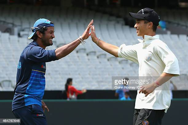 Dimuth Karunaratne of Sri Lanka high fives a cricketer from Geelong Grammar School after getting a wicket during an ICC Charity Session at Melbourne...