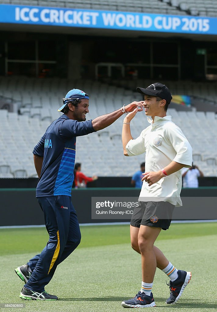 Dimuth Karunaratne of Sri Lanka high fives a cricketer from Geelong Grammar School after getting a wicket during an ICC Charity Session at Melbourne Cricket Ground on February 24, 2015 in Melbourne, Australia.