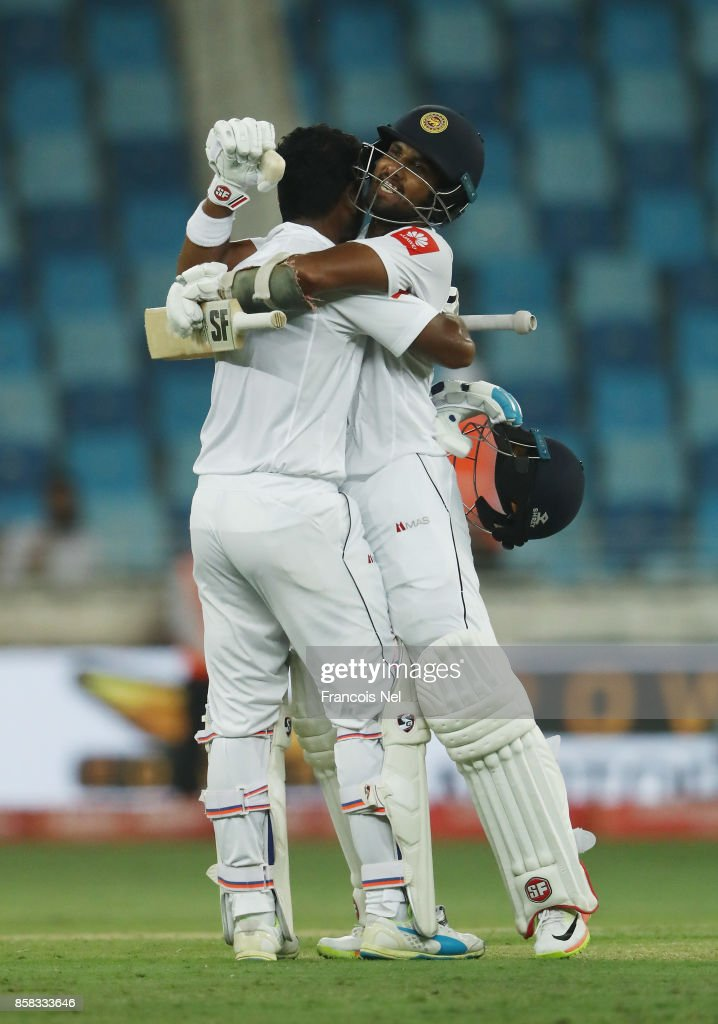 Dimuth Karunaratne of Sri Lanka is congratulated by Dinesh Chandimal of Sri Lanka after reaching his century during Day One of the Second Test between Pakistan and Sri Lanka at Dubai International Cricket Ground on October 6, 2017 in Dubai, United Arab Emirates.