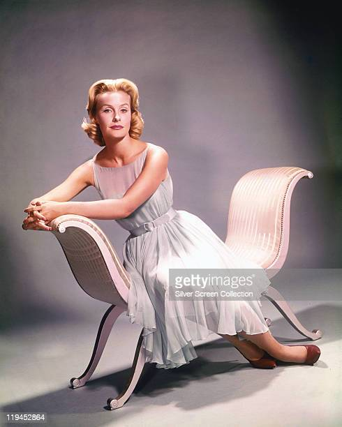 Dina Merrill US actress and socialite wearing a white sleeveless dress while sitting on a chair with two arm rests but no back circa 1955