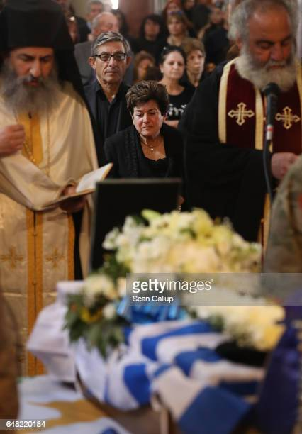 Dina Mita looks on as soldiers stand next to the small coffin that contains the remains of her brother Georgiou Theodoulos Theodoulou during his...