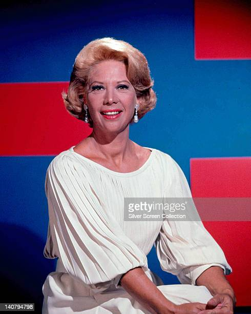 Dinah Shore US singer and actress wearing a white pleated top with a round neckline in a studio portrait against a red and blue background circa 1960