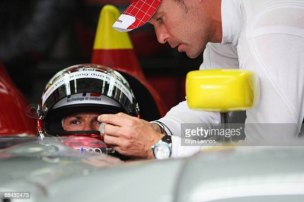 Dindo Capello of Italy talks with team mate Tom Kristensen of Denmark as he prepares to drive the Audi Sport Team Joest R15 TDI during qualifying for...