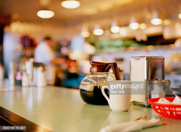 Diner counter top with coffee pot and cup next to napkin dispenser