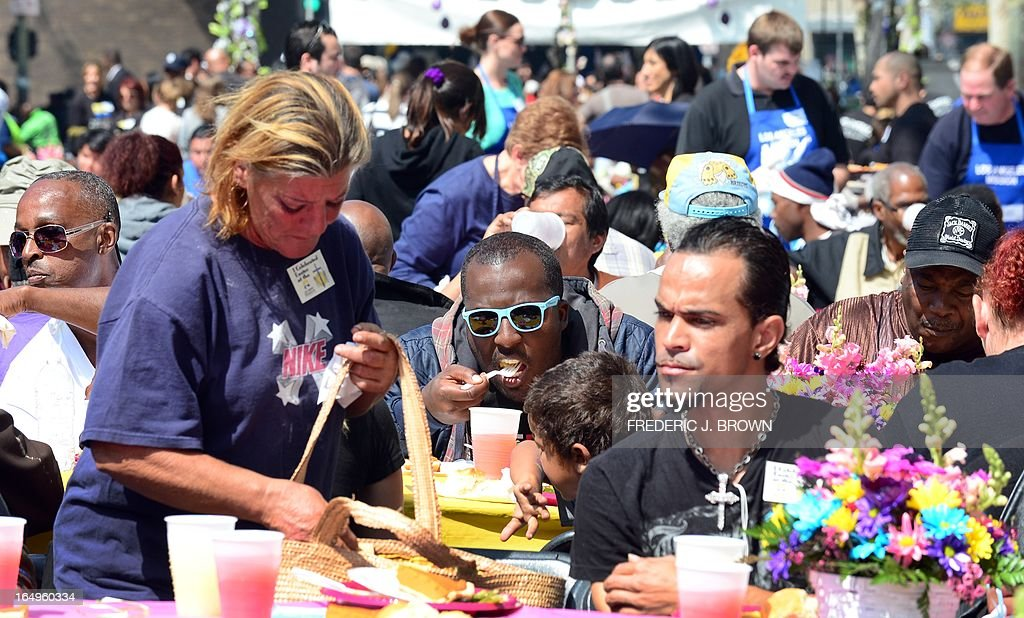 Diners enjoy their lunch at the Los Angeles Mission's Good Friday event on Skid Row on March 29, 2013 in Los Angeles, California. Celebrities and volunteers joined together in giving something back to this community of the homeless, among the largest in the US, who were fed a fully-prepared meal and had the opportunity to be given foot washing and hygiene kits. Foot washing, a symbolic ritual of humbleness and respect derived from Jesus Christ's washing of his disciples feet at the Last Supper, was offered by the Los Angeles Health Center and volunteers. AFP PHOTO/Frederic J. BROWN