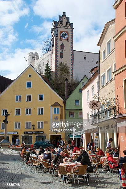Diners on Reichenstrasse with colourful old buildings and Hohes Schloss (High Castle) in background.