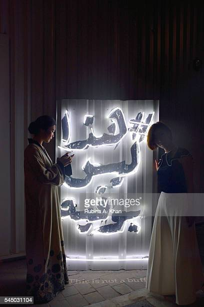 Diners posing for pictures with the Arabic signage of the Ramadan iftar popup at Alserkal Avenue on July 4 2016 in Dubai United Arab Emirates