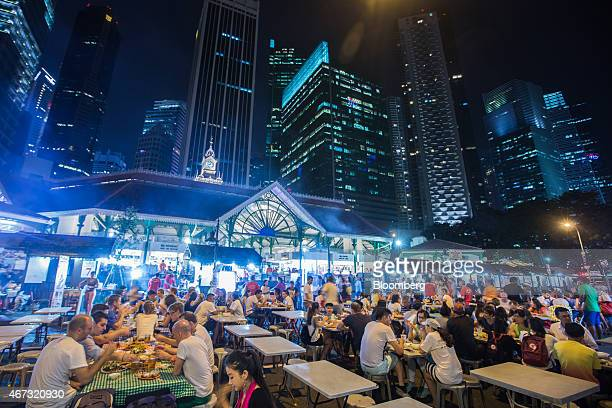 Diners sit at restaurant tables at the Lau Pa Sat food court as commercial buildings stand illuminated at night in the central business district city...