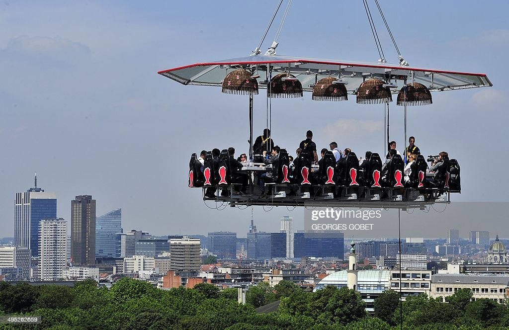 Diners take lunch suspended in the air on June 2, 2014 above the Parc du Cinquantenaire in Brussels.'Dinner in the sky' is an 'unique occasion' to discover Brussels's high cuisine and enjoy a spectacular view of the city from the air. 22 guests, strapped into their chairs with harnesses, sit around the mini kitchen where a 'starred' chef prepares and serves the meals and the wine. Brussels wants to become an essential actor of the European gastronomic scene. With its 19 starred restaurants, the EU capital has now more stars than Berlin, Rome, or Milan. 'Brussels in the Sky' takes place until June 29th at the Parc du Centenaire, close to the European area. Italy is the guest of honour at this 3rd edition. AFP PHOTO/ GEORGES GOBET