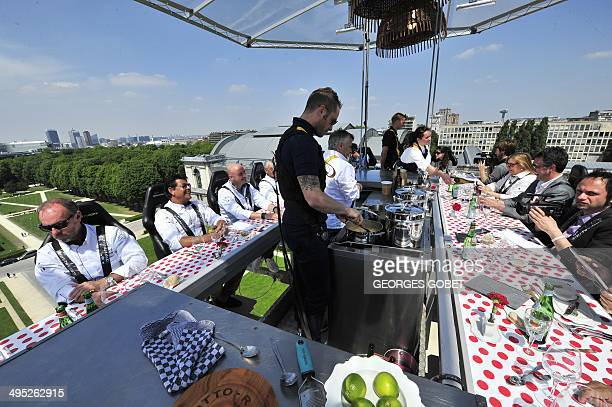 Diners take lunch suspended in the air on June 2 2014 above the Parc du Cinquantenaire in Brussels'Dinner in the sky' is an 'unique occasion' to...