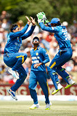 Dinesh Chandimal and Tillakaratne Dilshan of Sri Lanka celebrate their wicket of Kane Williamson of New Zealand during game five of the One Day...