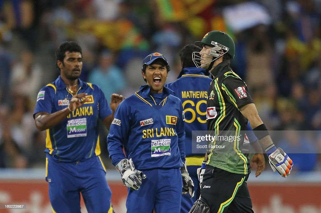 <a gi-track='captionPersonalityLinkClicked' href=/galleries/search?phrase=Dinesh+Chandimal&family=editorial&specificpeople=4884949 ng-click='$event.stopPropagation()'>Dinesh Chandimal</a> of Sri Lanka celebrates as <a gi-track='captionPersonalityLinkClicked' href=/galleries/search?phrase=Glenn+Maxwell&family=editorial&specificpeople=752174 ng-click='$event.stopPropagation()'>Glenn Maxwell</a> (R) of Australia walks from the field after the final ball of the game during game two of the Twenty20 International series between Australia and Sri Lanka at the Melbourne Cricket Ground on January 28, 2013 in Melbourne, Australia.