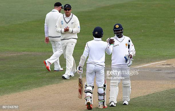 Dinesh Chandimal of Sri Lanka is congratulated by his captain Angelo Mathews on scoring 50 runs during day five of the First Test match between New...