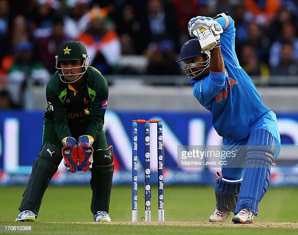 Dinesh Karthik of india hits the ball towards the boundary as Kamran Akmal of Pakistan looks on during the ICC Champions Trophy Group A match between...
