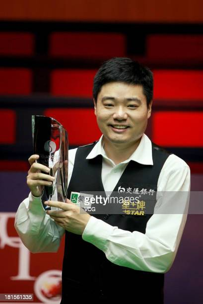 Ding Junhui of China poses with the trophy after winning the final match against Xiao Guodong of China on day seven of the 2013 World Snooker...