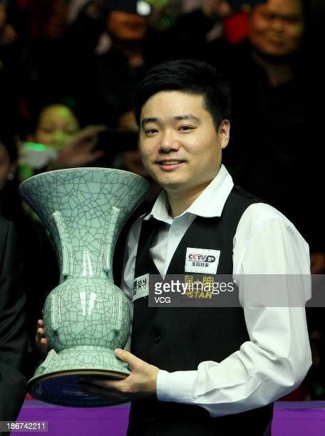 Ding Junhui of China poses with the trophy after winning the final match against Marco Fu of Hong Kong during the 2013 International Snooker...