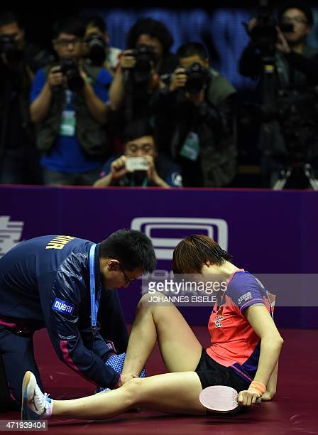 Ding Ning of Chinareacts in pain during her women's singles final match against Liu Shiwen of China at the 2015 World Table Tennis Championships at...