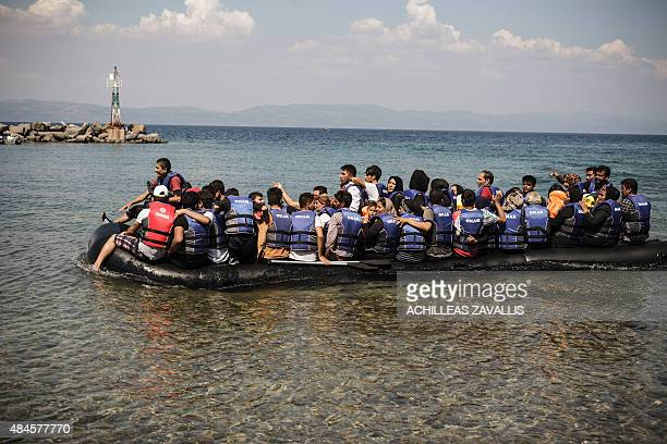A dinghy carrying Afghan Syrian and Iranian migrants arrives in the port of the village of Sikaminea on the Greek island of Lesbos on August 20 2015...