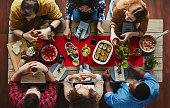 High angle view of young people sitting at table and having dinner