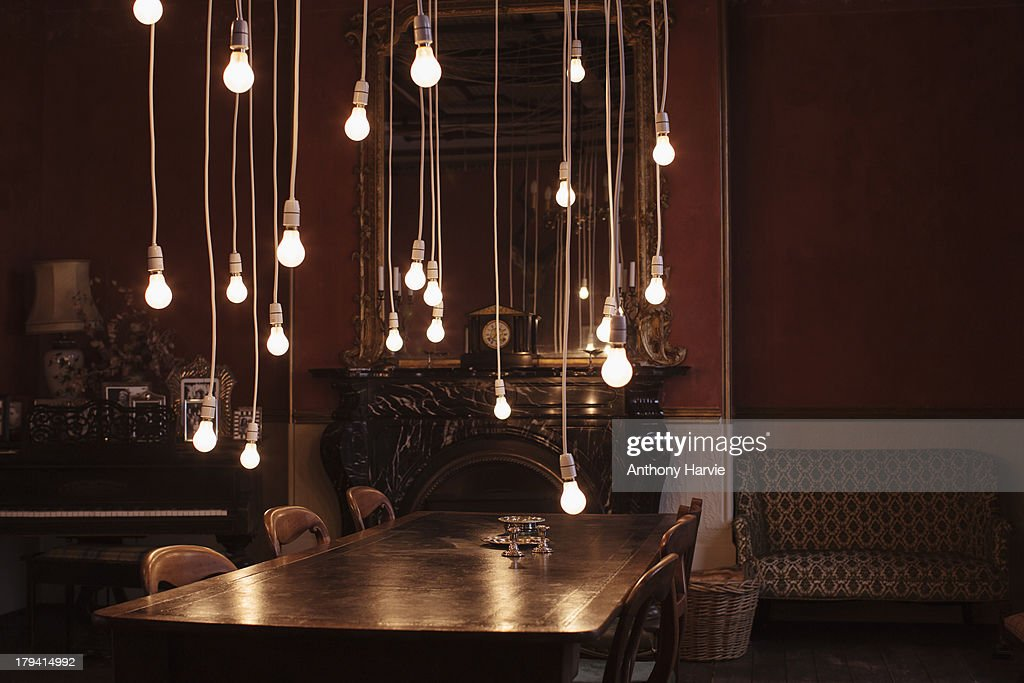 Dining room with hanging lightbulbs : Stock Photo