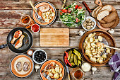 top view. Dining table with a variety of dishes, grilled chicken legs, fried potatoes with vegetables in a frying pan, salad and snacks on a wooden table,
