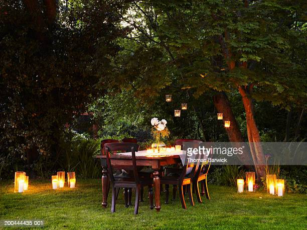 Dining table with candles and flowers, dusk, outdoors