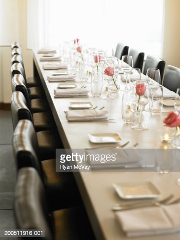 Dining table with place settings, candles and centerpieces : Stock Photo