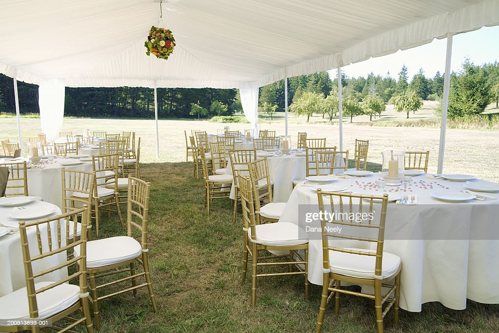 Dining tables and chairs under canopy outdoors : Stock Photo