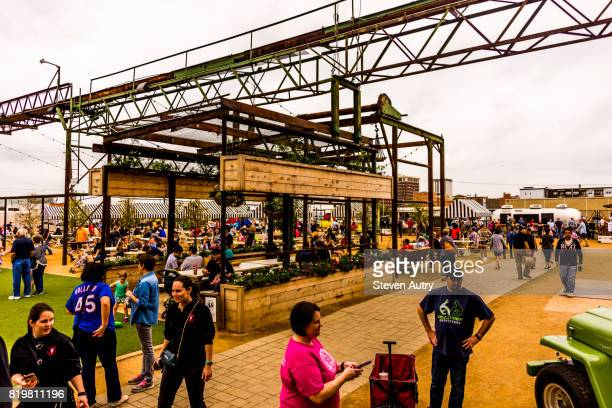 WACO, TX, USA  MARCH 18, 2017: Dining tables in the food services area of Magnolia Market with food trucks in the background.