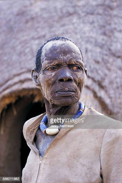 A Dinka man with dry weather beaten wrinkled face wearing a large blue decorative necklace South Sudan 1997