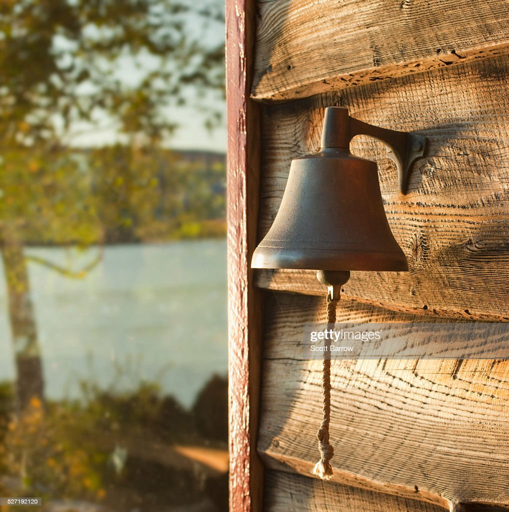 Dinner bell on wall of summer cottage : Foto de stock