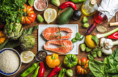Dinner cooking ingredients. Raw uncooked salmon fish with vegetables, rice, herbs, lemon, artichokes, spices and bottle of rose wine on white ceramic board over wooden background, top view, horizontal