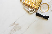 Glamorous fashion items and a glass of champagne. White marble copy space.