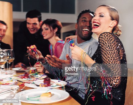 Dinner guests playing with streamers : Stock Photo