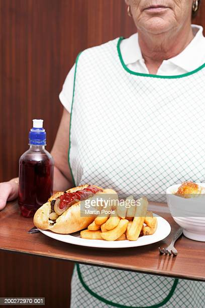 Dinner lady carrying tray with baguette and chips, mid section