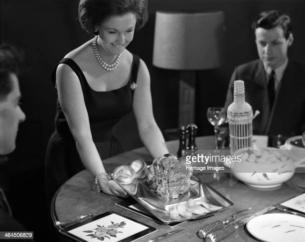 Dinner served 1964 In an early 1960s advertising shot a model serves up roast beef and Yorkshire Puddings