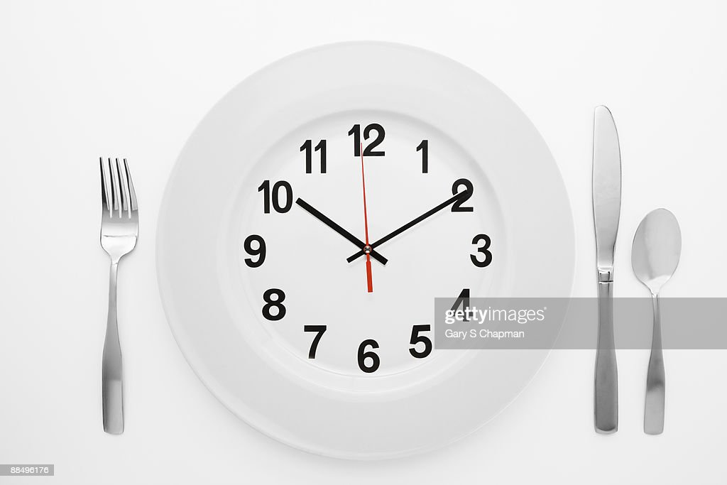 Dinner setting with clock on plate : Stock Photo