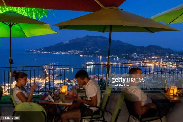 Dinner time, blue hour, Zakynthos illuminated port seen between dining tourists.Ionian  Islands Greece