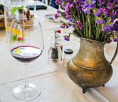 flower on dinning table with glass of wine