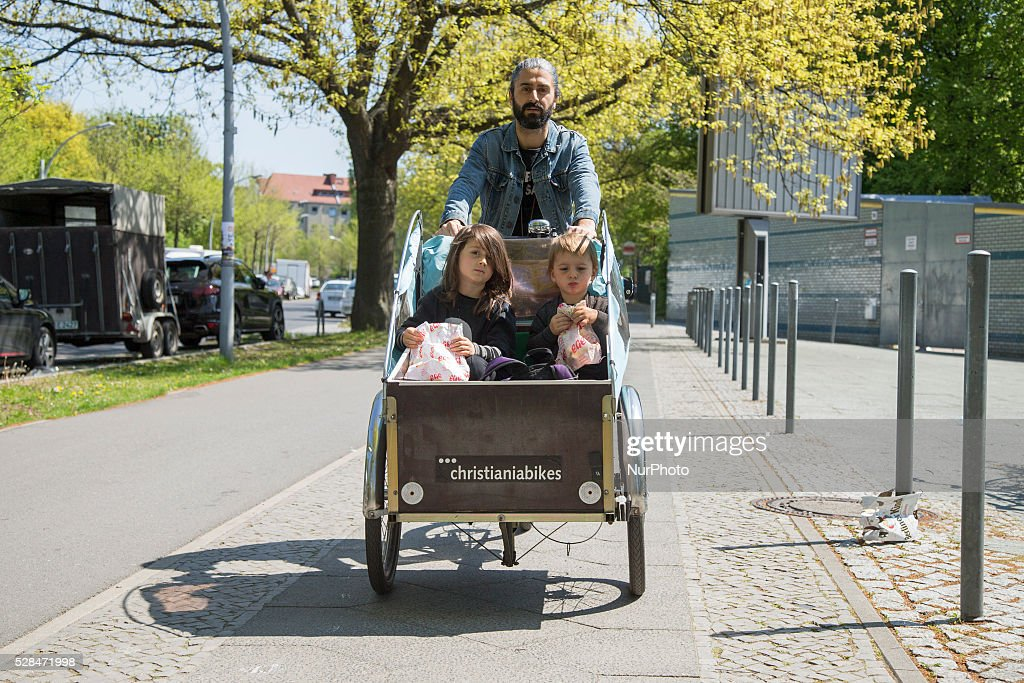Dino from Greece carries his children Achilles and Vanya in a child bike trailer during Father's Day in the Neukoelln district in Berlin, Germany on May 5, 2016.
