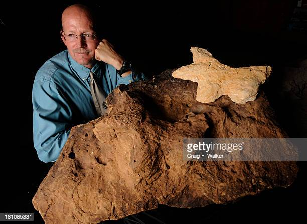 dino_052108_CFW Manual High School science teacher Kent Hups poses for a portrait with the first Jurassic Period track of an armored dinosaur known...
