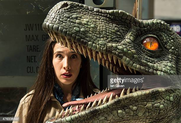 A dinosaur attendant emerges from a shipping container surrounded by dinosaurs during the 'Jurassic World' take over at Waterloo Station on June 8...