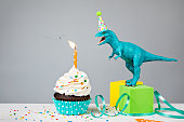 Toy Dinosaur blowing out a Birthday candle with cup cake on a gray background